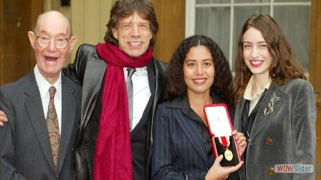 Em 2003, Mick recebeu no Palácio de Buckingham o título de Cavaleiro. Aqui ao lado do pai e das filhas, Karis e Elizabeth